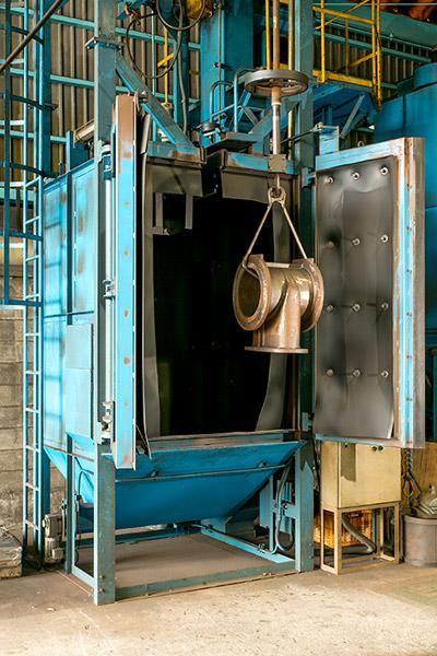 【ハンガー式ショットブラスト】直接製品を吊るし、ショットを当てる機械です。大きめの製品に使用します。