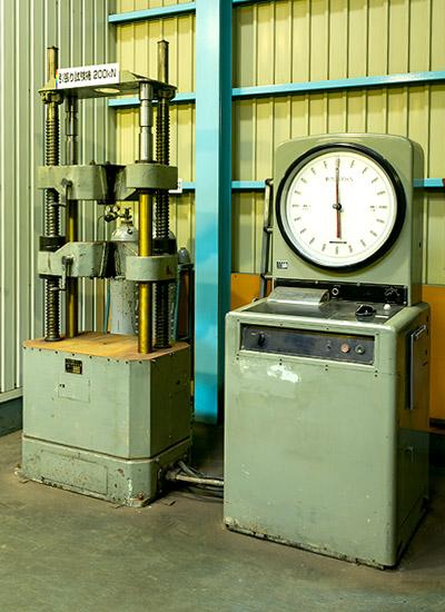 【引張試験機】棒状の試料をちぎれるまで上下に引っ張り、必要な強度が出ているかを検査する機械です。